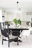 Armchair with black-painted wooden frame and white shell chair at table in open-plan, fitted kitchen