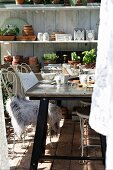 White metal chairs, fur rug and breakfast table in greenhouse