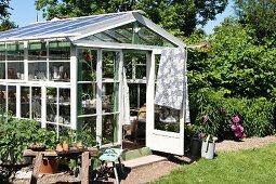 Sonnenbeschienenes Gewächshaus mit Sprossenverglasung in blühendem Garten