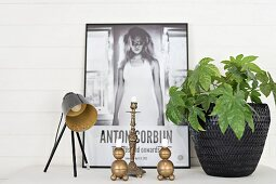 Retro table lamp, brass candlestick, house plant in black wicker pot and poster