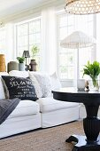 Black round table and white sofa with scatter cushions in front of standard lamp with white fabric lampshade