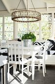 White-painted table, chairs and bench below wrought iron candle chandelier in conservatory