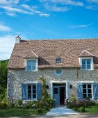 Renovated stone house with herbaceous borders and window shutters painted blue-grey