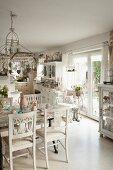 Weiss lackierte Flohmarktmöbel in offener, mit Shabby Deko überladener Wohnküche