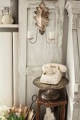 Cream vintage telephone on silver cake stand and old stool below candle sconce on decorative door with patinated paint