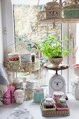 Schalen mit Blümchenmuster, selbstgemachte Marmeladen und Vintage Küchenwaage vor Fenster