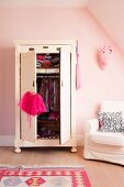 Child's clothing in wardrobe with open doors next to white armchair against pink-painted wall