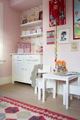 Child's bedroom with white furnishings, table and chairs against pink wall, chest of drawers and shelves in wallpapered niche