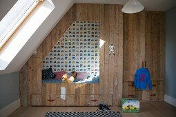 Cubby bed made from recycled wood in boy's bedroom with sloping ceiling