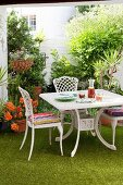 White table and chairs on artificial lawn in courtyard