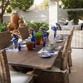 Solid wooden table set in white and blue and wicker chairs on terrace with sofa and terracotta pot in background