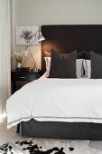 Scatter cushions and white throw on double bed with charcoal-grey headboard