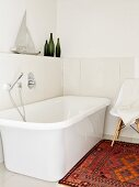 White, free-standing bathtub in bright bathroom with rug