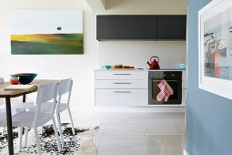 Bright, open-plan kitchen with floating base cabinets and dining area in foreground