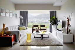Sofa and low sideboard in living room with view of landscape through glass wall