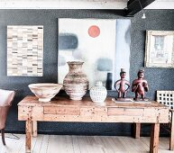 Exotic collection of vases and figurines on rustic wooden table below artworks on wall