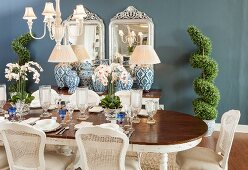 Elegantly set dining table, cane-back chairs and antique accessories