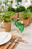 Detail of table set with green crystal glasses, woven place mats and potted geraniums