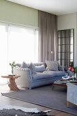 Organically shaped wooden side table next to elegant sofa in front of glass wall with floor-to-ceiling curtain