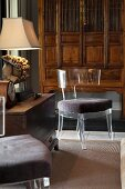 Plexiglas chair with chair seat in front of antique cabinet