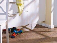 Mit Spiegelfliesen aufgepeppter Sockel unter den Küchenfronten
