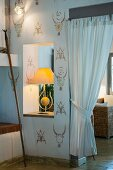 Table lamp in aperture in wall with ornate pattern stencilled on wall next to gathered white curtain in doorway