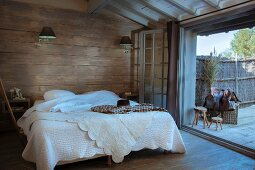 Double bed with white bedspread against wood-clad wall in rustic bedroom with open terrace doors