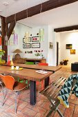 Rustic, modern dining table and retro chairs on terracotta floor below old, exposed wooden beams