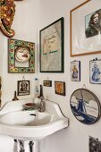 Corner sink below various pictures and ornaments on wall