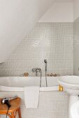 Small bathroom with white glass mosaic tiles under sloping ceiling