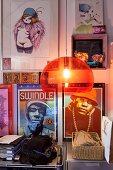 Orange, plastic, retro pendant lamp in front of gallery of pictures