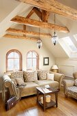 Traditional sofas in seating area below old wooden beams in attic