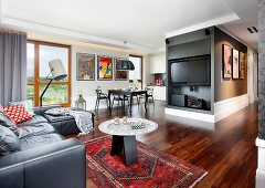 Leather sofa, side table on Oriental rug and flatscreen TV in open-plan lounge area with exotic-wood parquet floor