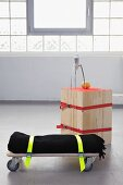 DIY stool made from wooden slats and seat made from blanket strapped to trolley