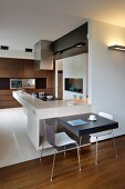 L-shaped kitchen counters with breakfast bar and integrated table for two; fitted cupboards with dark wooden fronts in background