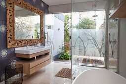 Glazed, floor-level shower opposite washstand and mirror with solid wooden frame carved with leaves in modern bathroom; view onto terrace through glass wall