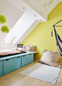 Minimalist bed below skylight and beanbag against yellow-painted gable-end wall in teenager's bedroom