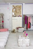 Old wooden crate and couch in wood-clad room with white chest of drawers next to open-fronted clothes rack