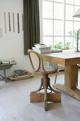Vintage swivel chair with bentwood frame at rustic, solid-wood table
