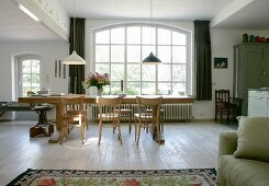 Long solid-wood table and simple chairs in front of arched lattice window in open-plan interior with rustic flair