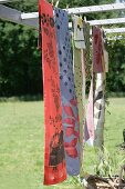 Table runners with various patterns hung on washing line in garden