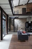 Couch in front of black spiral staircase against stone wall in loft apartment