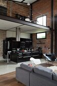 View past grey sofa and classic chair into black kitchen below gallery in loft apartment