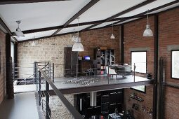 Gallery with stainless steel and wire rope balustrade in loft apartment with brick and stone walls