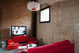 Red furniture in corner of room with exposed masonry walls and TV on metal sideboard