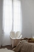 White Ron Arad armchair between floor-length curtains and bed