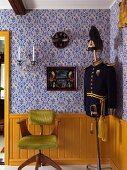Wooden swivel chair with lime green fur cover and tailors' dummy wearing old uniform against yellow-painted wainscoting below ornamental blue wallpaper