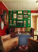Vintage leather armchair and antique leather couch around wooden trunk used as coffee table in corner of living room; walls in rich colours decorated with gallery of pictures