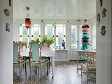 Turquoise-painted, wooden chairs with carved backrests at white dining table in rustic dining room with row of stained-glass windows