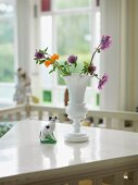 Garden flowers in white retro china vase and china cat on table